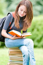 Young student girl sitting on pile of books Royalty Free Stock Photos