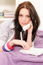 Young student girl speaking on phone lying Royalty Free Stock Photography