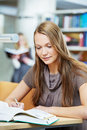Young student girl working with book in library Royalty Free Stock Photography