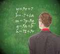 Young student looking at chalkboard with mathematics Royalty Free Stock Photo