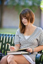 Young student outdoors writing college sitting on campus bench Royalty Free Stock Photos