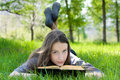 Young student reading book in park Royalty Free Stock Photo