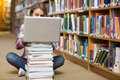 Young student sitting on library floor using laptop on pile of books in college Stock Photos