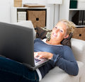 Young student using laptop while lying on couch Stock Images