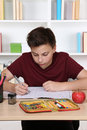 Young student writing in his exercise book at school Royalty Free Stock Photo