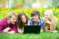 Young students group with computer outdoors Stock Images