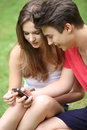 Young students reading a text message teenage boy and girl sitting on the grass on their mobile phone Stock Photography