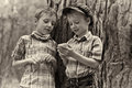 Young stylish boys browse the internet on mobile p two phone vintage postcard Royalty Free Stock Photo