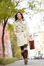 Young stylish female professional holding handbag wearing modern trench coat walking in urban city smiling happy multiracial asian Stock Image