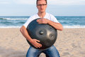 Young stylish guy sitting on the sand beach and holding a handpan or hang with sea On Background. The Hang is Royalty Free Stock Photo
