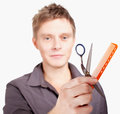 Young  stylish haircutter holding scissors and brush. Royalty Free Stock Image