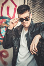 Young stylish man model posing in leather jacket and sunglasses. Royalty Free Stock Photo
