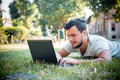 Young stylish man using notebook at the park Royalty Free Stock Photo