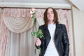 Young stylish shaggy and unshaven man in black leather jacket holds two wilted roses retro room Stock Photo