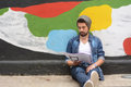 Young stylish student seated against a colorful wall latin urban style Stock Photos