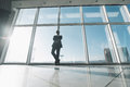 Young success business man standing satisfy against panoramic windows Royalty Free Stock Photo