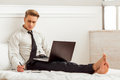Young successful businessman attractive blond in white classical shirt and dark tie making notes and using laptop while sitting on Stock Images
