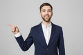 Young successful businessman pointing direction with finger over dark grey background. Copy space. Royalty Free Stock Photo