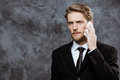 Young successful businessman speaking on phone over grey background. Royalty Free Stock Photo