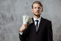 Young successful businessman in suit holding money over grey background. Royalty Free Stock Photo