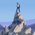 Young Successful businessman winner standing on peak mountain. Going to the top. Royalty Free Stock Photo