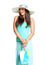 Young sun tanned woman dressed in a turquoise shirt and a straw hat holding colorful paper bags and smiling at the camera isolated Royalty Free Stock Photo
