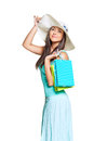Young sun tanned woman dressed in a turquoise shirt and a straw hat holding colorful paper bags and smiling at the camera isolated Stock Images
