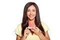 Young sun tanned woman with slice of watermelon dressed in a lite summer yellow dress holding smiling and looking at the camera Stock Photography