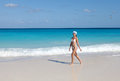 The young suntanned slender woman with a long fair hair in white sexual bikini goes on a peschenny beach against turquoise ocean Royalty Free Stock Image