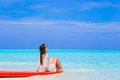 Young surfer woman at white beach on red surfboard Royalty Free Stock Photo