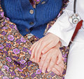 Young sweet doctor holds the old woman's hand Royalty Free Stock Photo