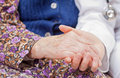 Young sweet doctor holds the old woman's hand Royalty Free Stock Photography
