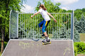 Young teeange girl on a ramp at a skate park balancing sideways her roller blades as she climbs to the top of steep slope Royalty Free Stock Photo