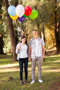 Young teen couple adorable with helium balloons in forest Royalty Free Stock Image