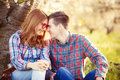Young teen couple in the spring blossom apple trees Royalty Free Stock Photo