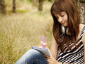 Young teen girl doing homework at the park Stock Photos
