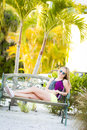 A young teen girl enjoying paradise while sitting on a bench under a palm tree Stock Image