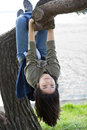 Young teen girl hanging on tree limb Royalty Free Stock Photos