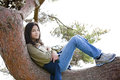Young teen girl relaxing on tree limb Stock Images