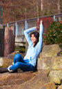 Young teen girl sitting on large boulders or rocks outdoors arms raised over head excited and happy biracial in blue shirt jeans Royalty Free Stock Image