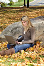 Young teen girl using laptop - autumn Stock Photos