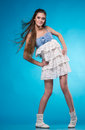 Young teen girl in a white lace dress joyful posing studio over blue background Stock Photo