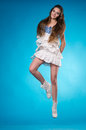 Young teen girl in a white lace dress jumping joyful studio over blue background Stock Image
