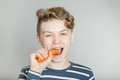 Young teenage boy biting a fresh raw carrot Royalty Free Stock Photo