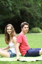 Young teenage couple enjoying the sunshine summer sitting back to back on grass in a lush green garden Stock Images