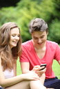 Young teenage couple laughing at an sms attractive sitting on the lawn in a park they have received on their mobile phone Royalty Free Stock Photos