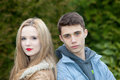 Young teenage couple posing back to back trendy looking at the camera with serious expressions as they pose outdoors in the garden Royalty Free Stock Photo