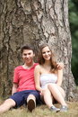 Young teenage couple sitting against a tree happy smiling attractive trunk enjoying summer day together out in nature Stock Photos
