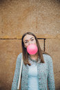 Young teenage girl blowing pink bubble gum portrait of beautiful brunette over a stone wall background Royalty Free Stock Photos