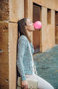 Young teenage girl blowing pink bubble gum portrait of beautiful brunette resting over a stone wall Royalty Free Stock Images